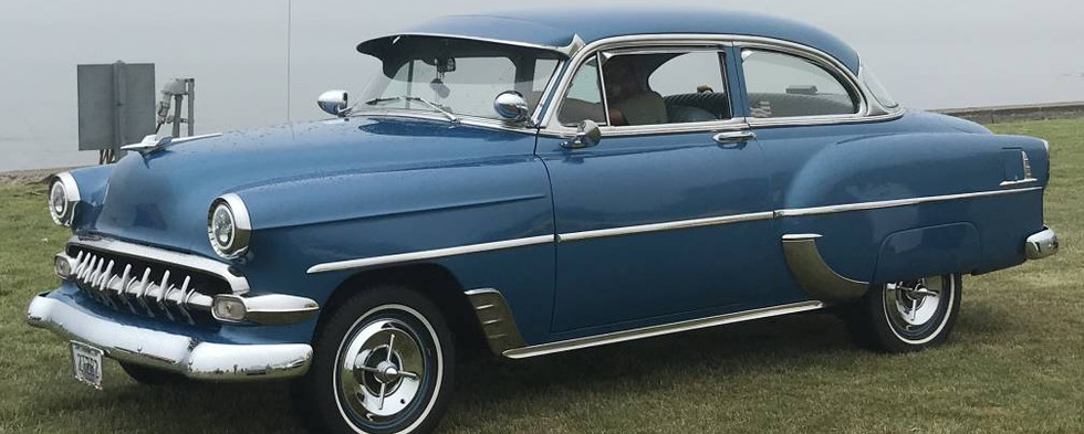 A mild custom '54 Chevy 210 rolls by the water's edge.  Note the dummy spotlights, windshield visor and extra teeth in the grille.
