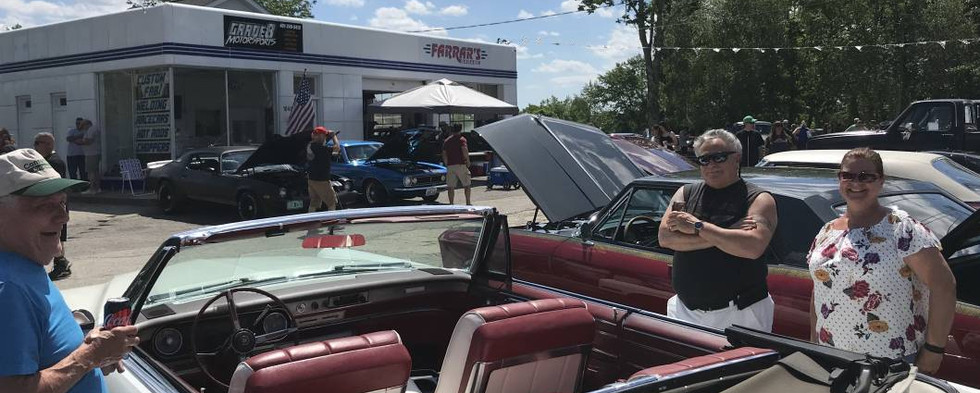 Rich (left) extolls the virtues of his '66 Cadillac convertible to a couple fascinated spectators.