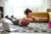 Young woman exercising at home in a livi
