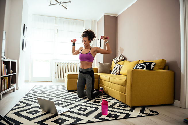 Young woman exercising at home with dumb