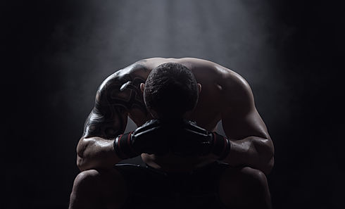 Boxer athlete sits with a drooping head