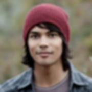 Jeune adulte au teint foncé et portant un bonnet, fixant la caméra