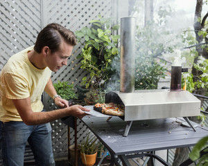 Tending to the UUNI Outdoor Pizza Oven