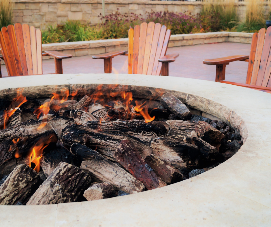 raised firepit with low fire and chairs in the background