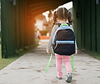 little girl with pigtails wearing a backpack walking to school