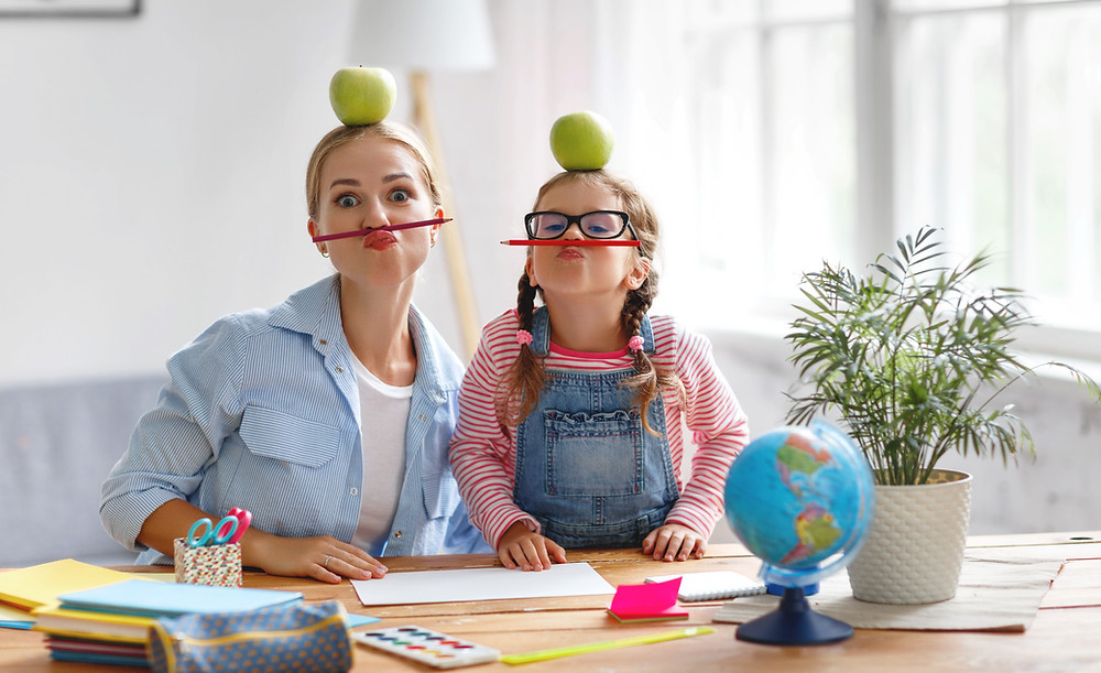 mom and daughter being silly while doing homework