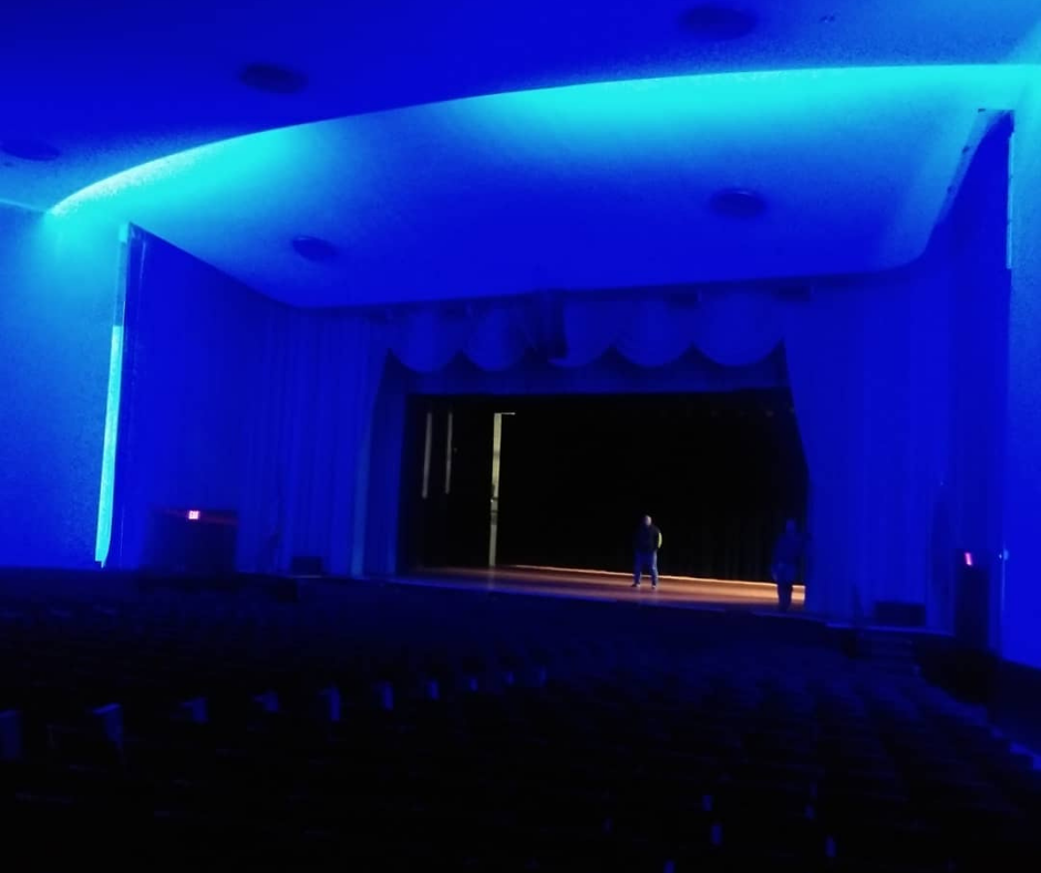 sturges-young auditorium and stage bathed in bright blue light