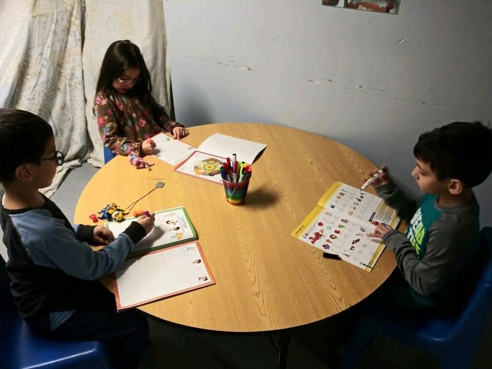 kids sitting around a table doing school work