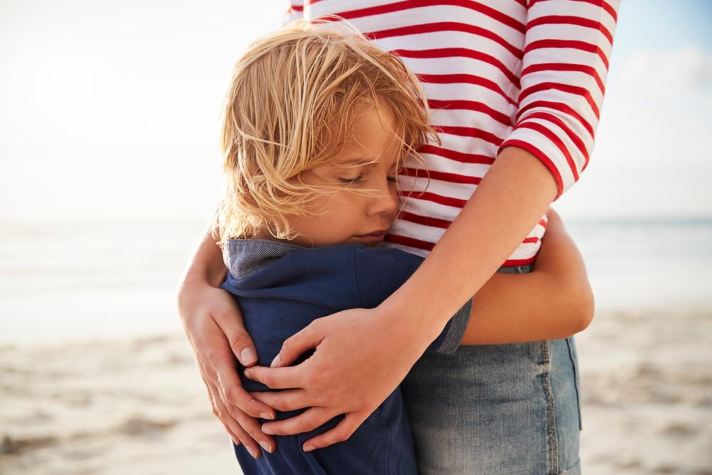 child hugging mom on beach