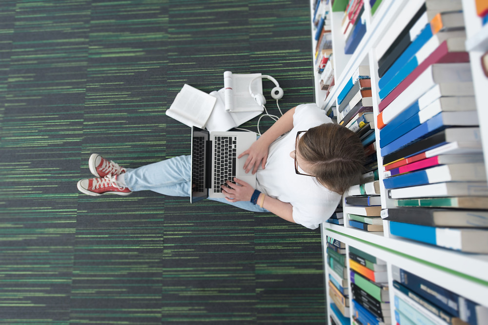 teen using laptop in library