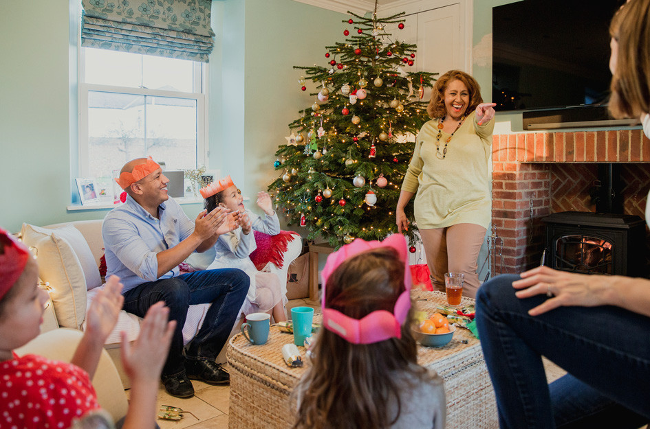 family playing a game in front of Christmas tree