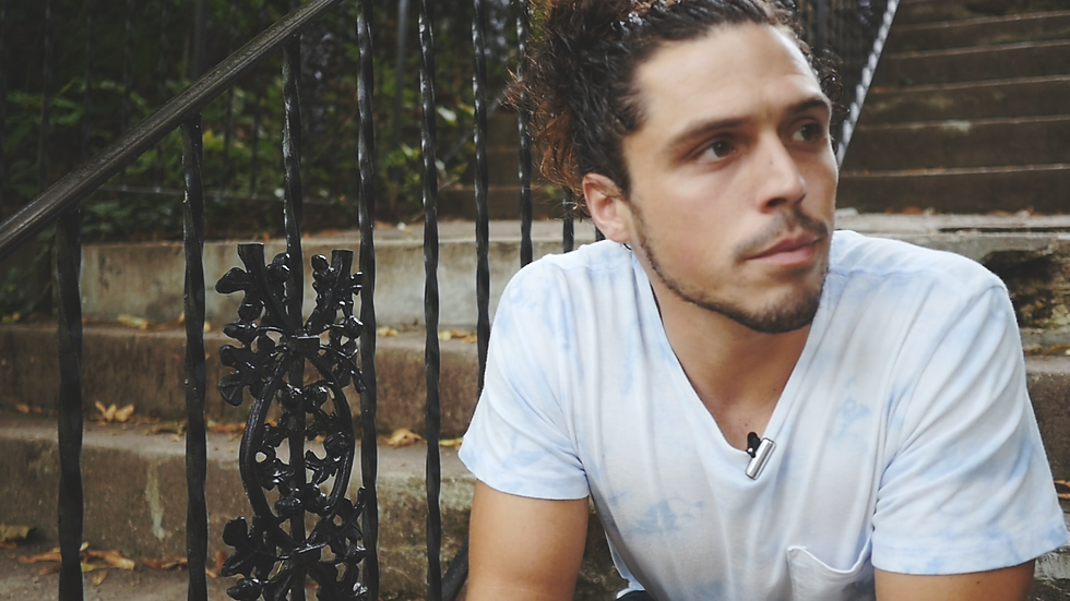 young man with bun in white t-shirt sitting on concrete steps with iron railing