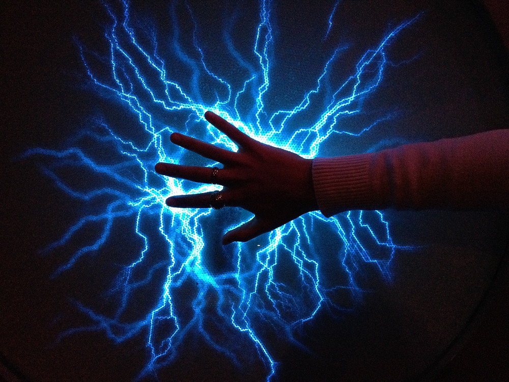 girls hand touching blue static electricity on screen
