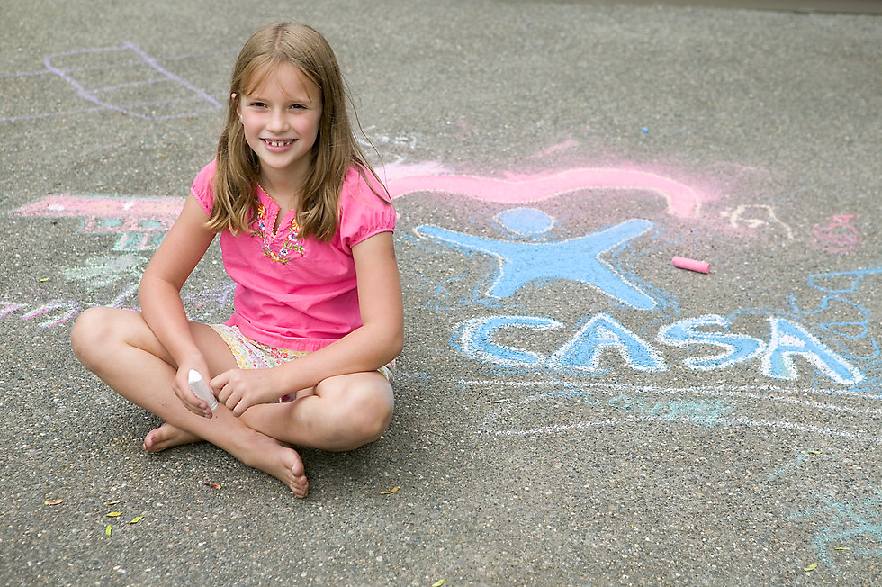 child in pink shirt sitting on the ground beside  chalk drawings
