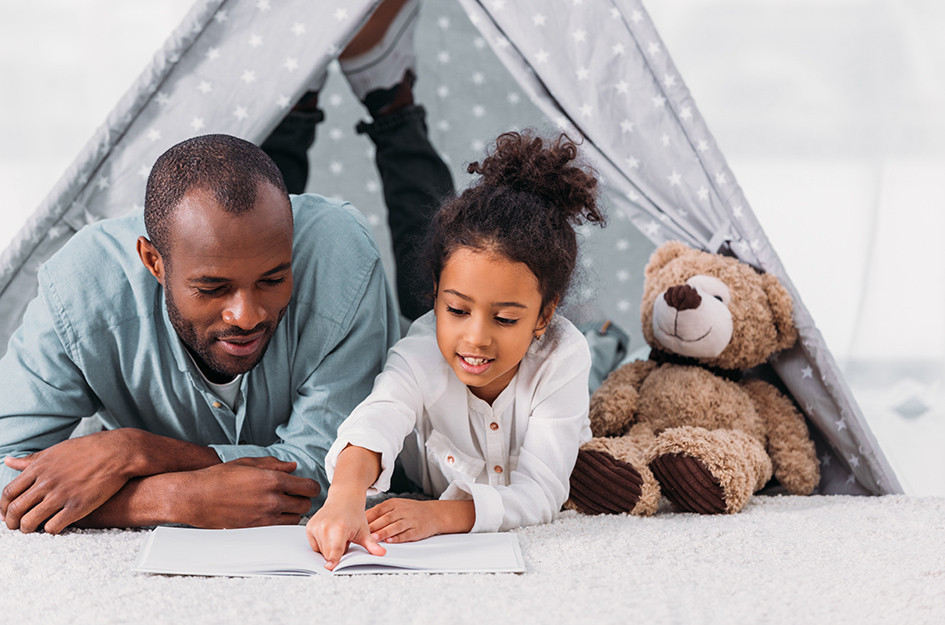 dad and daughter reading book in play tent