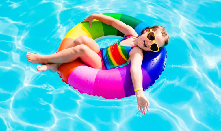 little girl with heart sunglasses floats on inner tube
