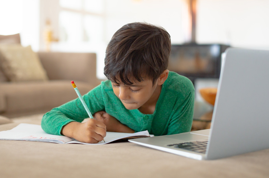 photo of young boy in green sweater doing homework with laptop