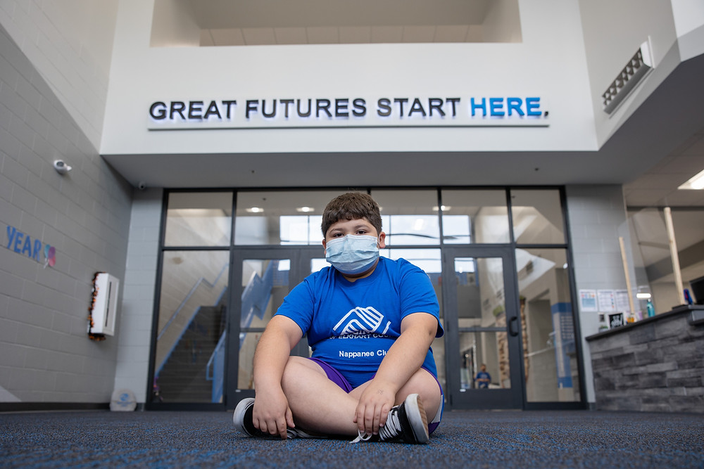 club member sits in front of great futures start here sign wearing face mask