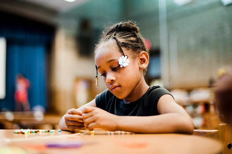 child making jewelry with beads