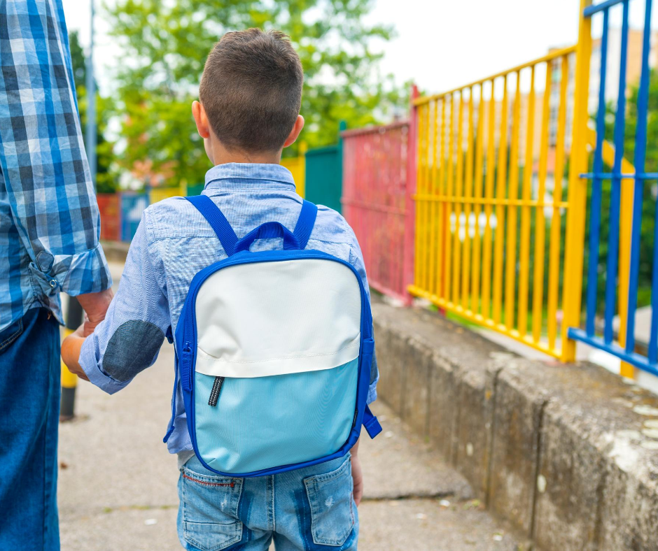 young boy with backpack holding adult's hand