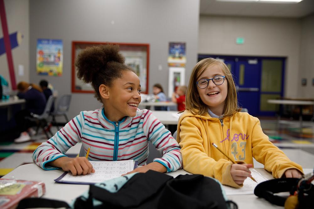girls laughing and doing homework