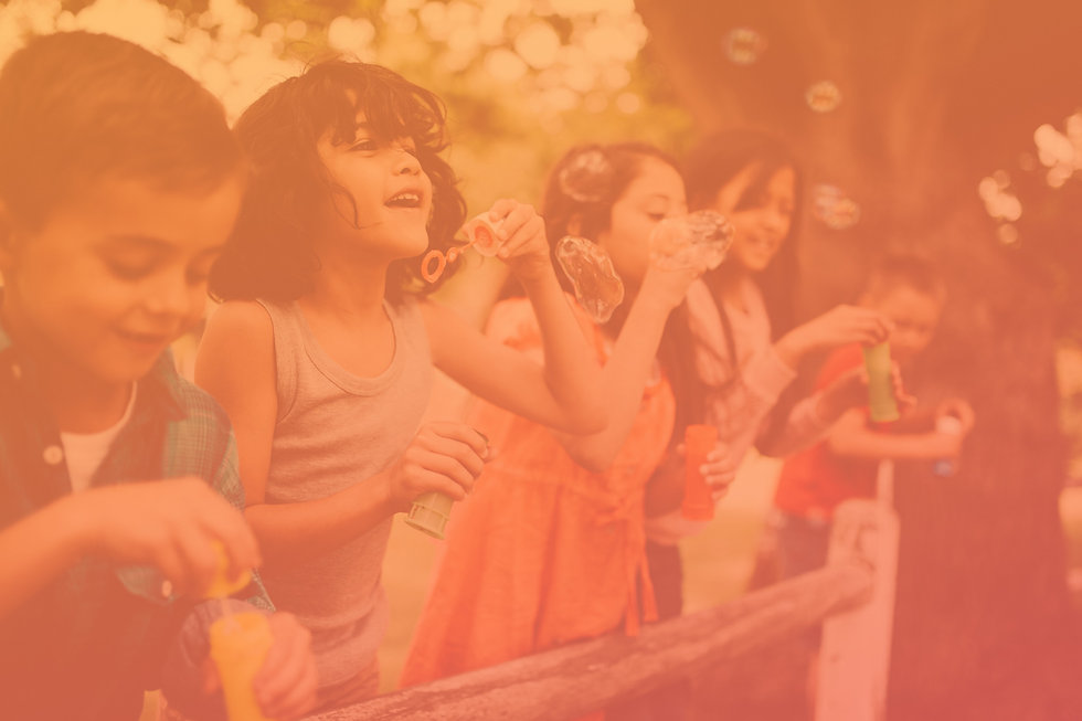 young latina girl with dark hair blowing bubbles with friends in summer