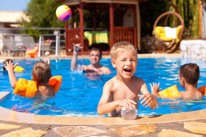children play in swimming pool on sunny day