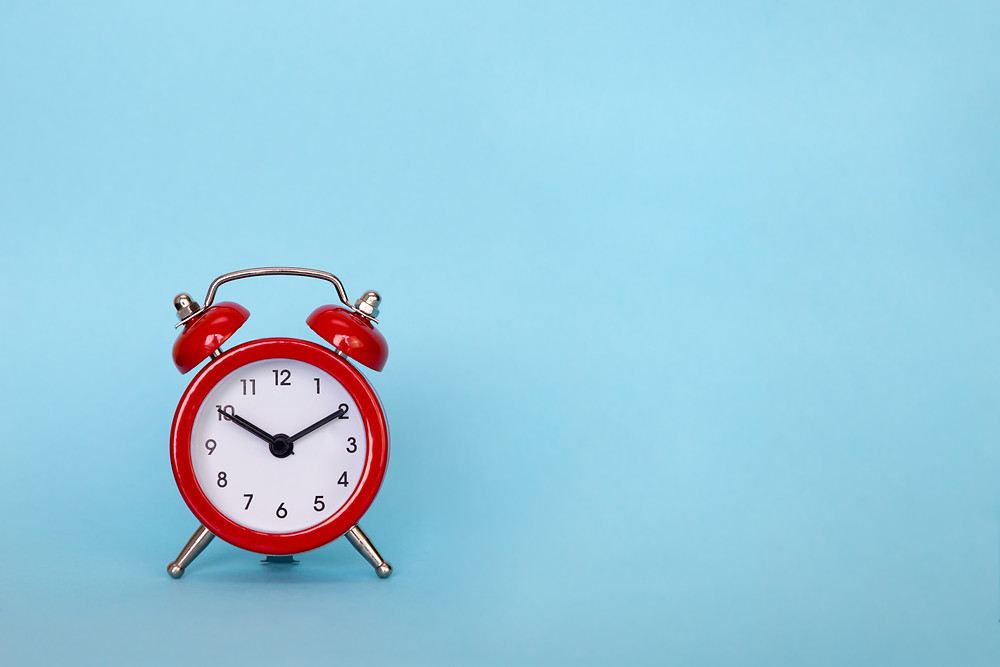 red alarm clock on a blue background