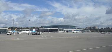 Luxembourg Findel Airport terminal gebouw met tarmac, Fokker 50 Cityjet vliegtuig en benzinevrachtwagen met wolken op een zonnige dag
