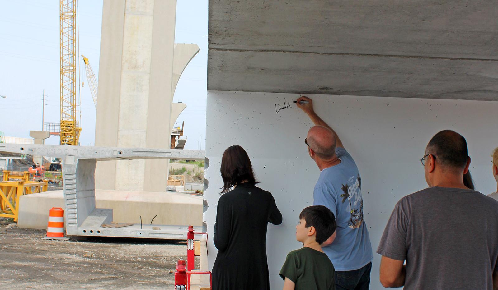 Sidewalk Talks attendees sign a bridge segment.