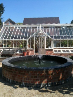 Greenhouse and raised pool with fountain in walled vegetable garden