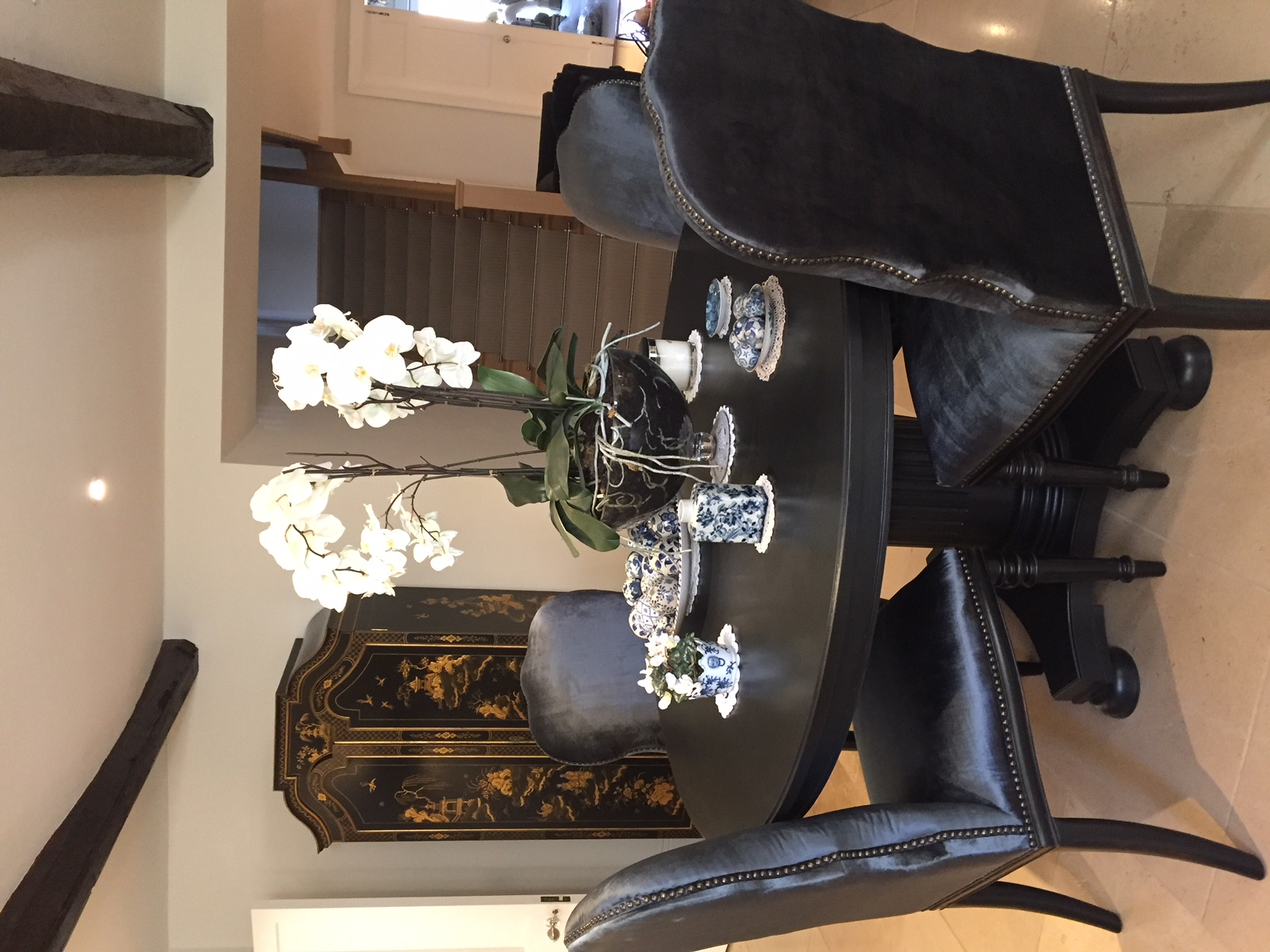 black dining room table and upholstered chairs featured decorative Chinoiserie cabinet