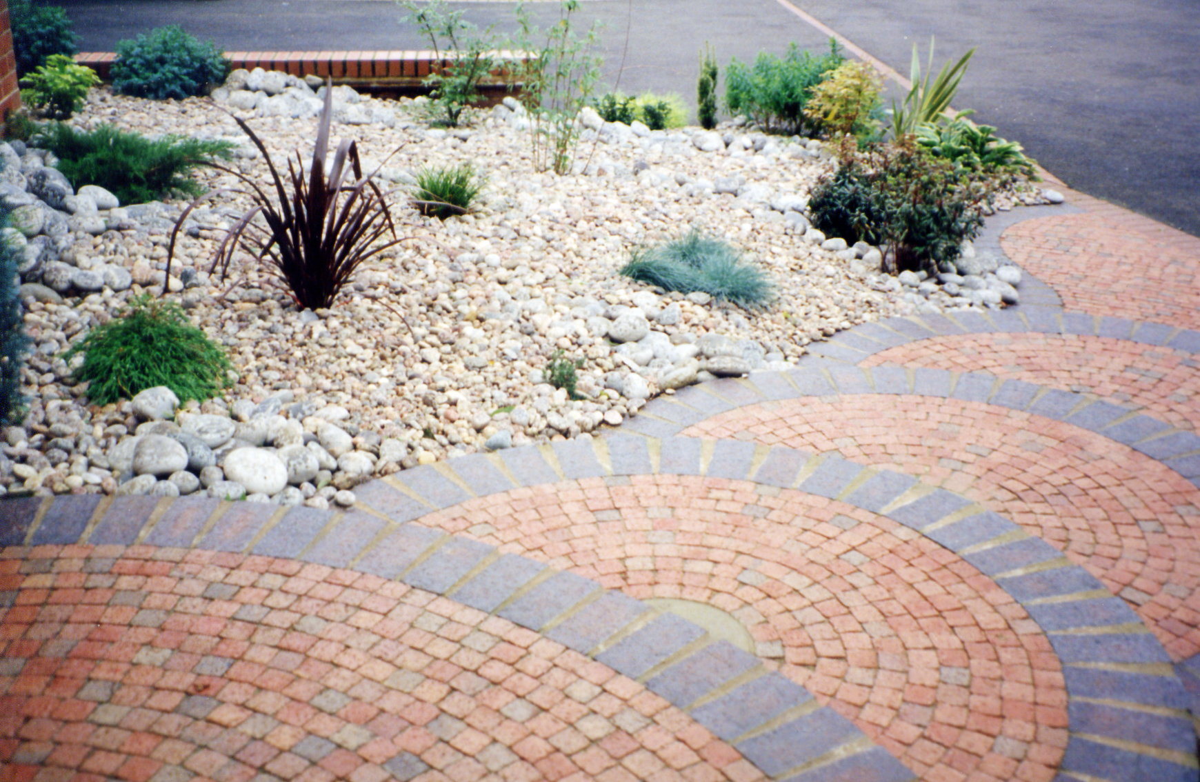 Curved front steps and evergreen planting in cobbles and boulders (2)