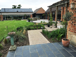 Barn conversion in Leicestershire with connecting pathway through a planting area