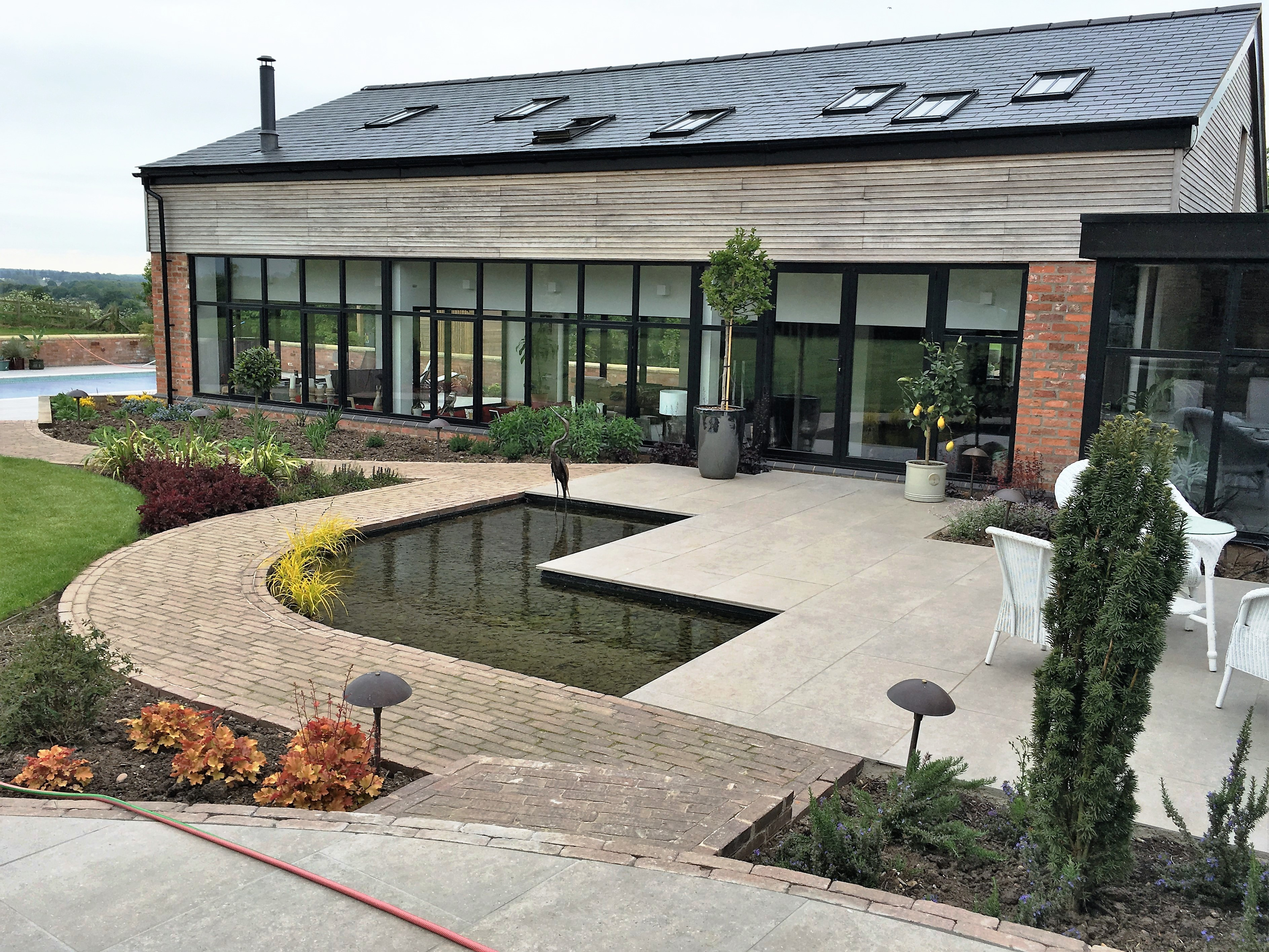 Barn conversion in Leicestershire L-shaped pond terrace