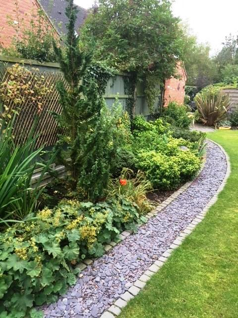 Slate path with block edgings bordering a perennial border
