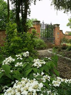 Mixed planting softening walls and entrance gates