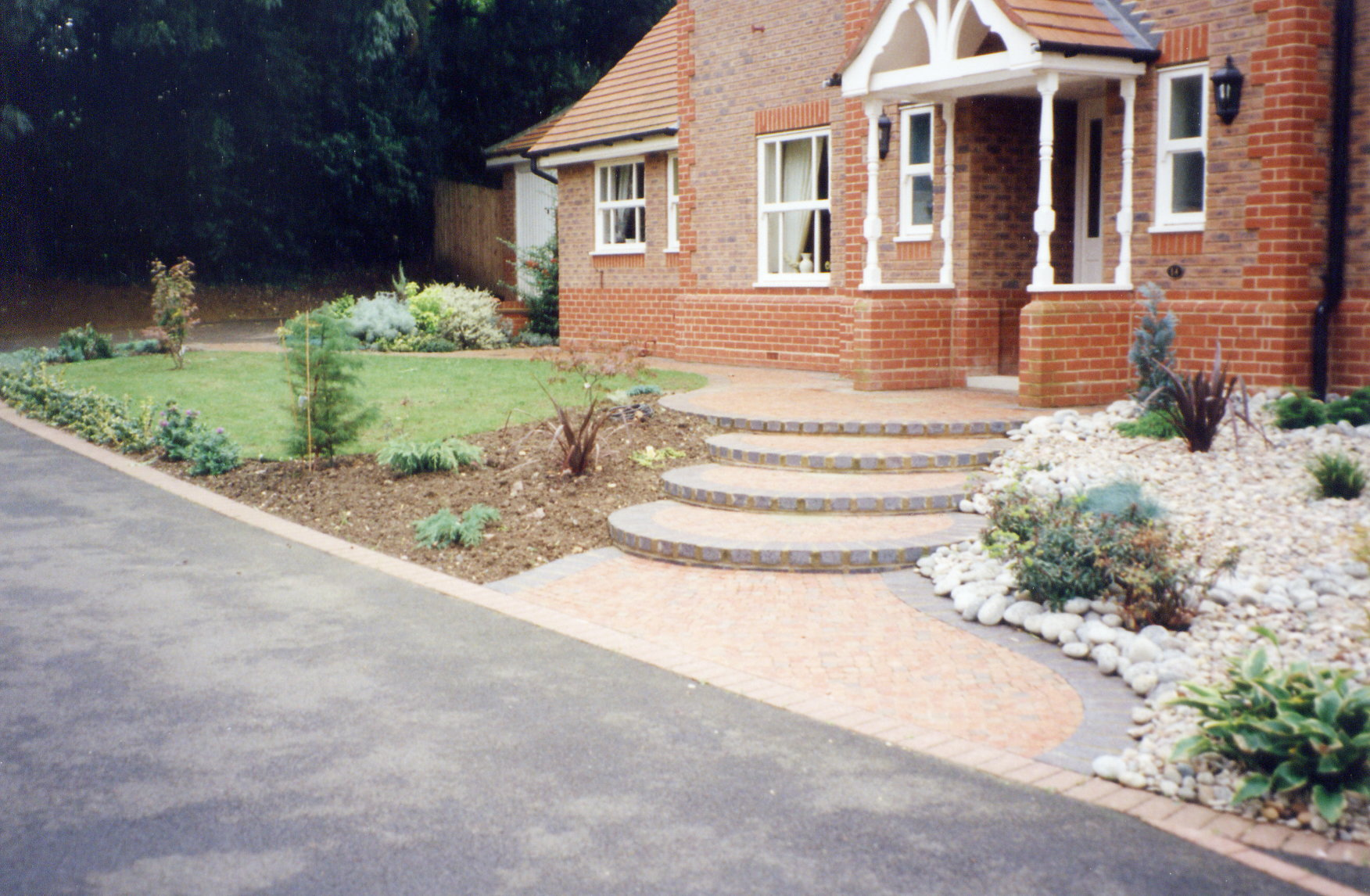 Curved front steps and evergreen planting in cobbles and boulders (1)