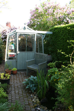 Old wooden greenhouse nestled amongst planting and wildlife pond