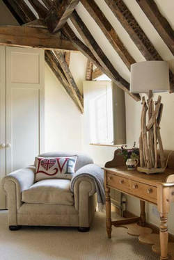 Comfy upholstered armchair in beamed cottage bedroom