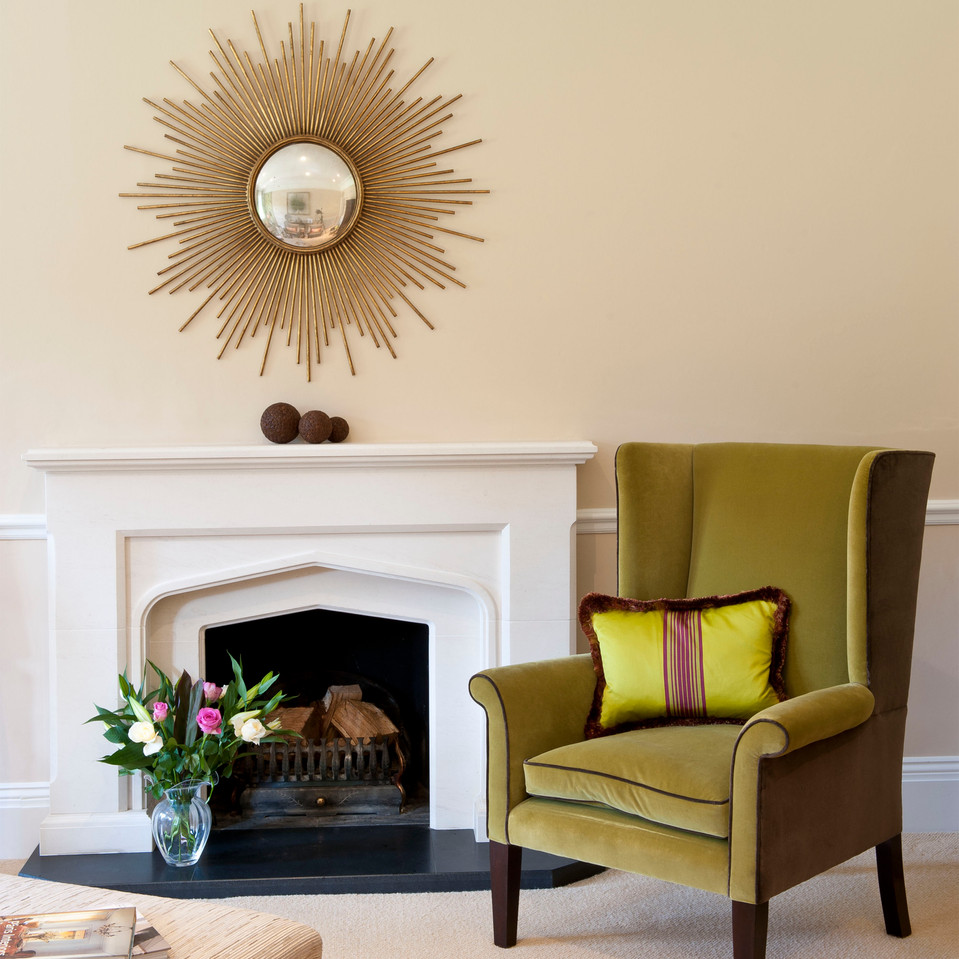 Armchair in green with lime green cushion in front of fireplace