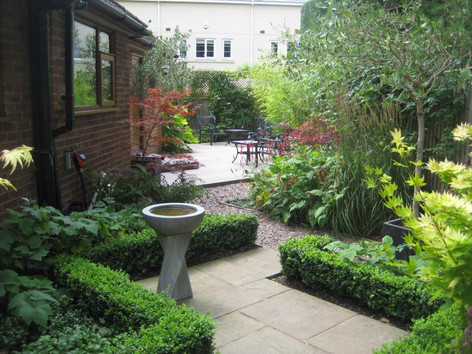 small paved courtyard garden with box he