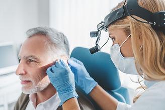 Ear Doctor looking at older man's ear