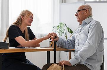 smiley-senior-man-conversing-with-nurse_