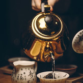 person-holding-gold-teapot-pouring-white