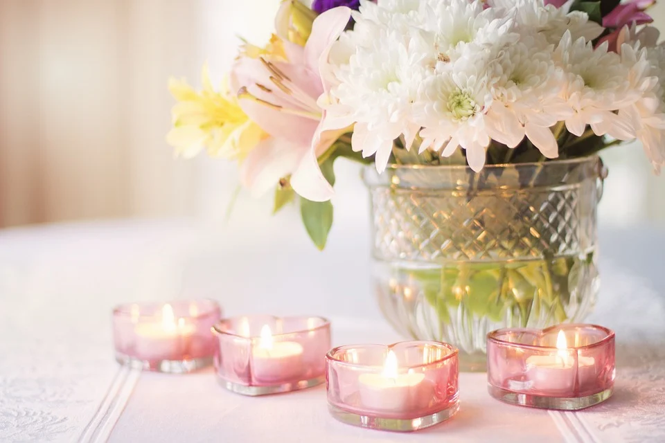 Centerpiece with white flowers and candles in hearth shaped containers