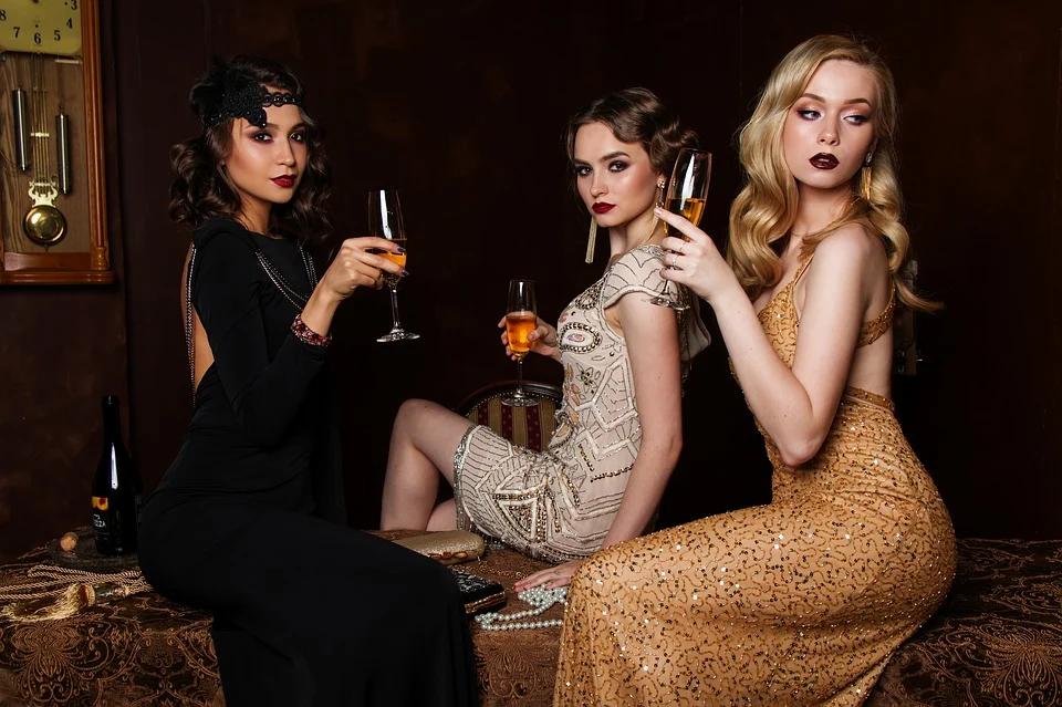 3 women in elegant dresses drinking wine in a dark room
