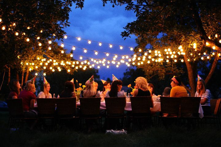 People enjoying a party in the afternoon with lights hanging above
