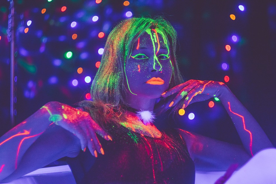fluorescent paint covering a girl in a dark room