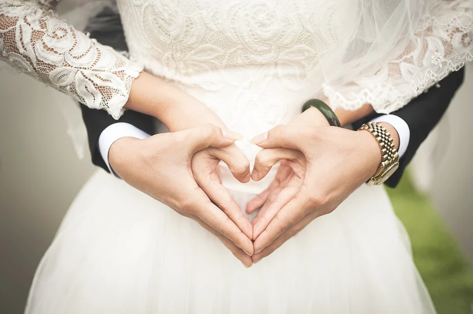 Bride and groom holding hands in a heart shape